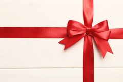 Gift red bow and ribbon on a white wooden background royalty free stock photography