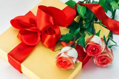 Gift, red bow and roses. Gift tied up by red bow and roses Stock Photography