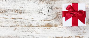 Gift with red bow on rustic wood in flat lay view. Giftbox with red bow on rustic wood in flat lay view Stock Images