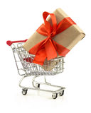 Gift with red bow in the shopping cart. Isolated on white background Stock Images