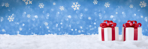 Gift Red bow on snow, banner. Blu background Stock Photography