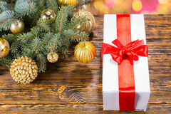 Gift with Red Bow on Table with Festive Pine Bough Stock Photos