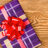 Gift with a red bow. On a wooden background Royalty Free Stock Image