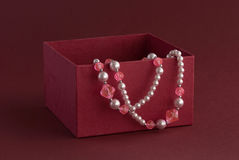 Gift in red box. Red box with beads on colored background Stock Images