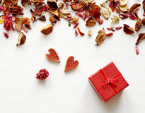 Gift red box with a bow and two red hearts in an environment of dry fragrant flowers Royalty Free Stock Photography