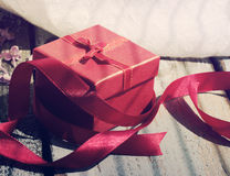 Gift red box with a bow on a wooden background. Royalty Free Stock Photography