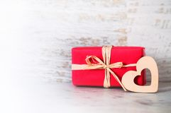 Gift in red box and a light heart on wooden background Valentine. `s day Stock Images