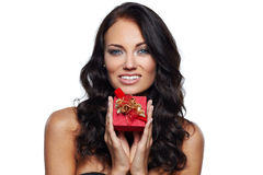 Gift in a red box. Smiling young woman holding a gift in a red box isolated on white stock photos