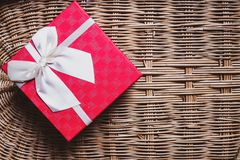 Gift red box with white ribbon on woven bamboo wood background cozy and warm home welcome concept idea.  stock image