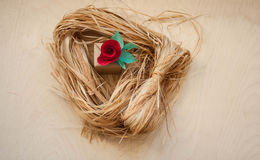 Gift and Red paper flowers. Gift and Red  paper flowers on the wooden background and bast. Cut from paper. Place for your text Stock Photo