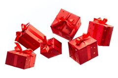 Gift in red paper tied with satin ribbon with bow. Surprise in flying boxes wrapped in red gift paper with bow on white background. Concept of holidays and royalty free stock photography