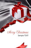 Gift with red ribbon. Christmas gift with red ribbon, on silver satin material Royalty Free Stock Images