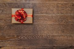 Gift with a red ribbon and bow on a dark wooden background. Christmas decorations Stock Image