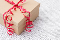 Gift with red ribbon on a knitted background Stock Photos
