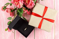 Gift with red ribbon, ring in box and pink flowers Stock Image
