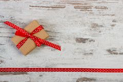 Gift with red ribbon for Valentines Day, copy space for text on old rustic board. Wrapped gift with red ribbon on old board, decoration for Valentines Day, copy Royalty Free Stock Image