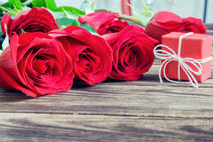 Gift and red roses on a wooden background Royalty Free Stock Photo