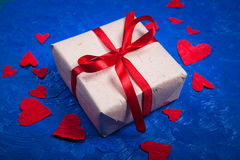 Gift  with red tape and a lot of red paper hearts on  blue backg Royalty Free Stock Photo