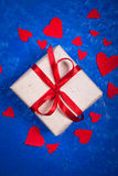 Gift  with red tape and a lot of red paper hearts on  blue backg Stock Images