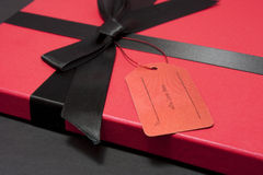 Gift with ribbon. Gift or present with red box in a box with black ribbon Royalty Free Stock Image