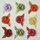 Gift ribbon bows of different colors. High angle shot of some satin gift ribbon bows of different colors on an off-white background, with a retro effect Royalty Free Stock Photos