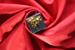 Gift with ribbon placed in the center of a spiral of red satin fabric royalty free stock image
