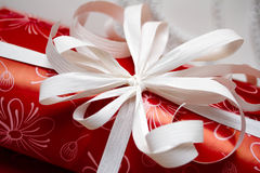 Gift ribbon on red paper. Hand tied gift ribbon on red paper Royalty Free Stock Photo