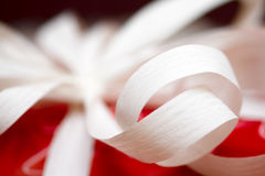 Gift ribbon on red paper. Hand tied gift ribbon on red paper Royalty Free Stock Photography