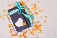 Gift with ribbon on the table. Pencil and sketchbook. Royalty Free Stock Images