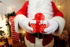 Gift rode doos met stippen met een boog in de handen van Santa Cl Stock Foto