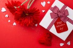 Gift, rode gerberas en een hart op een rode achtergrond stock afbeeldingen