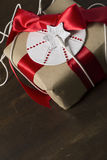 Gift rustic, with red ribbon and star label Royalty Free Stock Photo