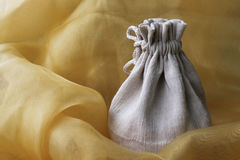 Gift sack. White gift sack  on yellow cloth Royalty Free Stock Photography