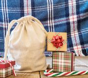 Gift sack, presents, and candy canes on rustic wooden surface wi stock photos