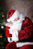 Gift for Santa. Santa Opening Present full of sparkling wonder stock image