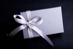 Gift With A Satin Ribbon. Gift wrapped in gray paper, with a silver-gray satin ribbon tied in a bow at one end. Isolated on a black background royalty free stock image
