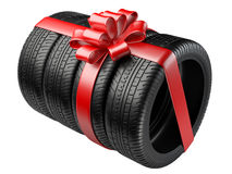 Gift set four tyres with a wrapped red ribbon and bow. Royalty Free Stock Photos