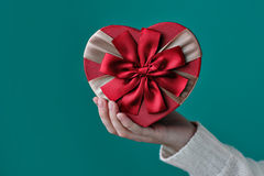 Gift in the shape of a heart in his hand Royalty Free Stock Image