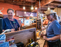Gift shop employee waits on a customer at Arizona-Sonora Desert. Tucson, AZ, March 21, 2016: Gift shop employee waits on customer at Arizona-Sonora Desert Museum Royalty Free Stock Photos