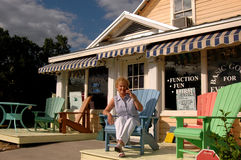 Gift shop owner. A gift shop owner sitting in front of her store on the phone Royalty Free Stock Photo