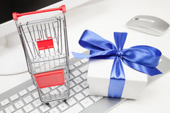 Gift and shopping cart with computer Royalty Free Stock Photo