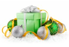 Gift in snow with bow and  green balls Royalty Free Stock Photo