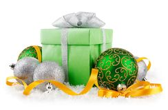Gift in snow with bow and  green balls Stock Photography