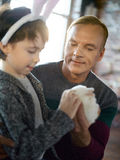 Gift for son. Little boy cuddling Easter rabbit held by his father royalty free stock photo