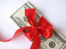 Gift Stack of $ 100 bills. Stack of $100 money with red ribbon in white background Royalty Free Stock Photos