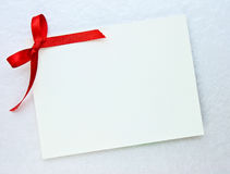 Gift tag. Blank gift tag tied with a bow of red satin ribbon Stock Photo