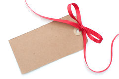 Gift tag. Blank gift tag with a red satin ribbon bow Royalty Free Stock Images