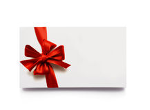 Gift tag. Blank gift tag tied with a bow of red satin ribbon. Isolated on white, with soft shadow Stock Photography