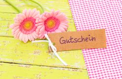 Gift tag with german word, Gutschein, means voucher or coupon and pink flowers for Valentine or Birthday. Beautiful pink gerbera flowers with card with german Royalty Free Stock Image