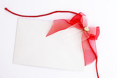 Gift tag with red bow. White gift tag with red bow on white background Royalty Free Stock Image